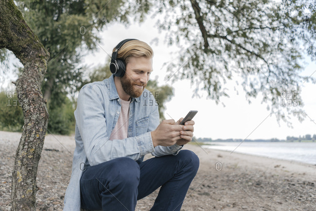 Germany- Dusseldorf- smiling man with headphones using smartphone on the beach