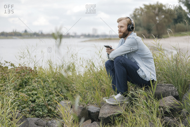 Germany- Dusseldorf- man listening music with headphones and smartphone in nature