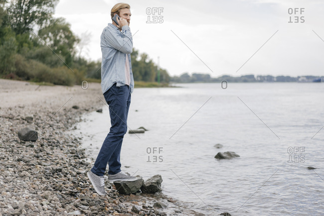Germany- Dusseldorf- man on the phone standing at riverside looking at view