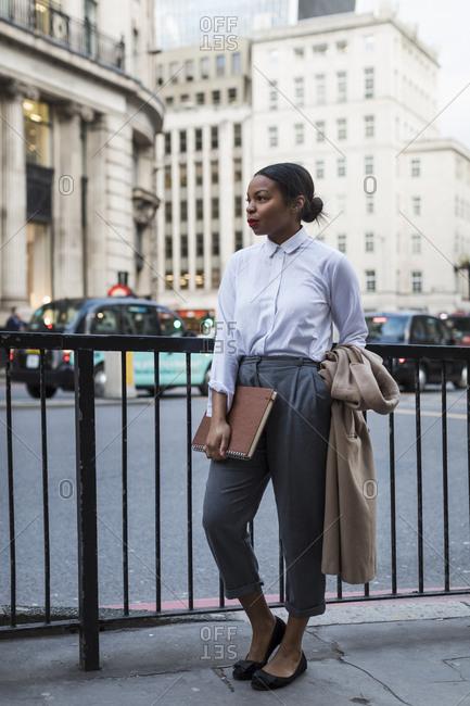 UK- London- fashionable businesswoman waiting on the street