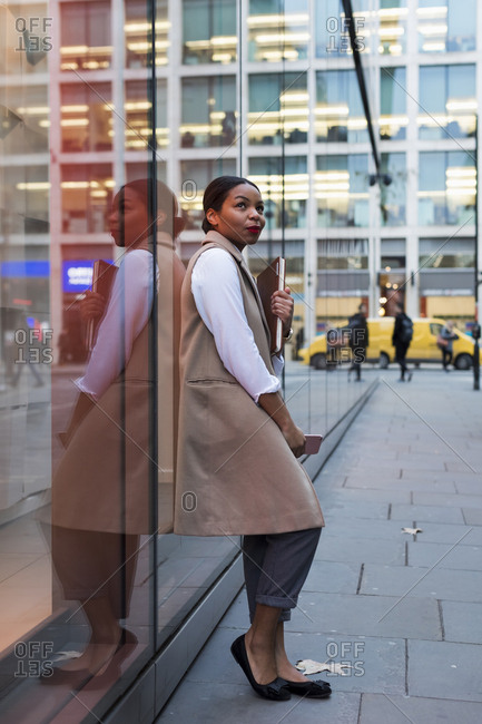Smiling businesswoman leaning against glass pane looking up