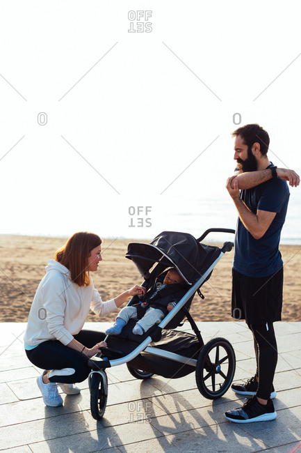 Couple doing sport with a baby in stroller