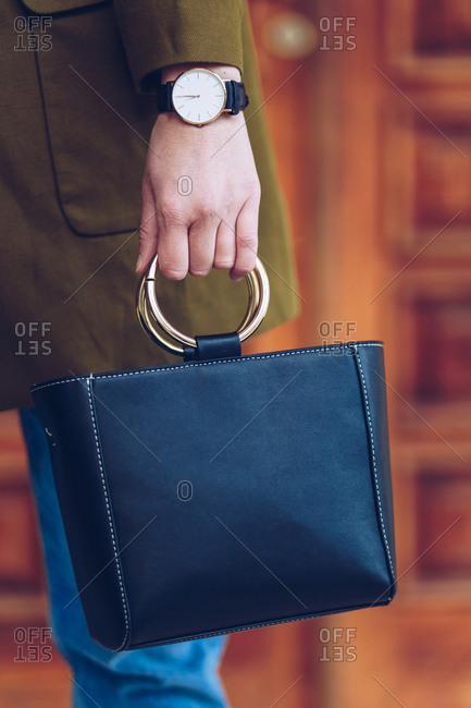 Street fashion portrait detail of professional woman's black leather purse and elegant wristwatch