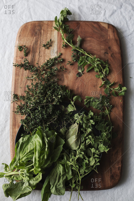 Green herbs and vegetables on a cutting board