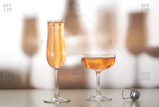 Glasses of rose or pink champagne with shadows on background