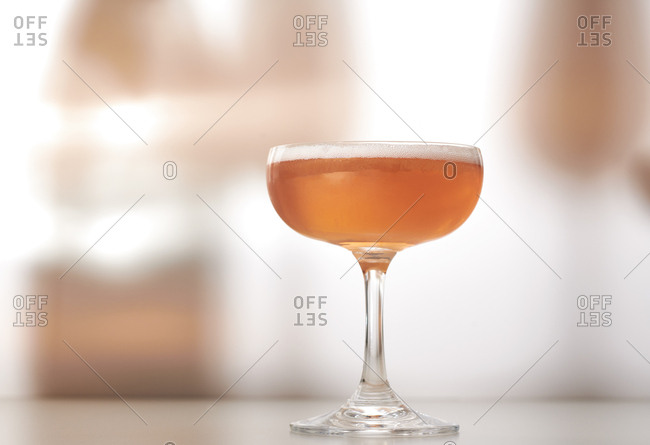 Glass of rose or pink champagne (in vintage glass) with shadows on background
