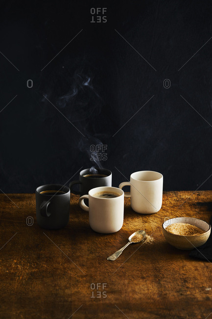 Four coffees on a table with steam and sugar