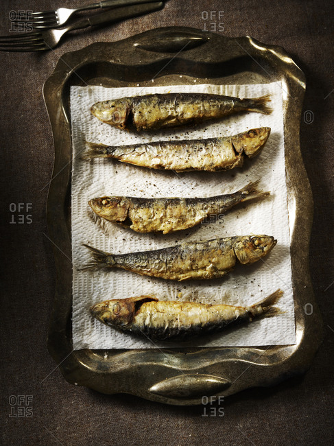 Five fried sardines on a metal platter