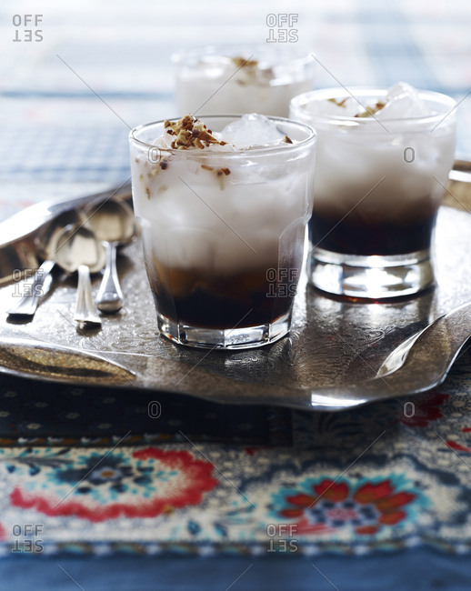 Three brown and white drinks on a tray