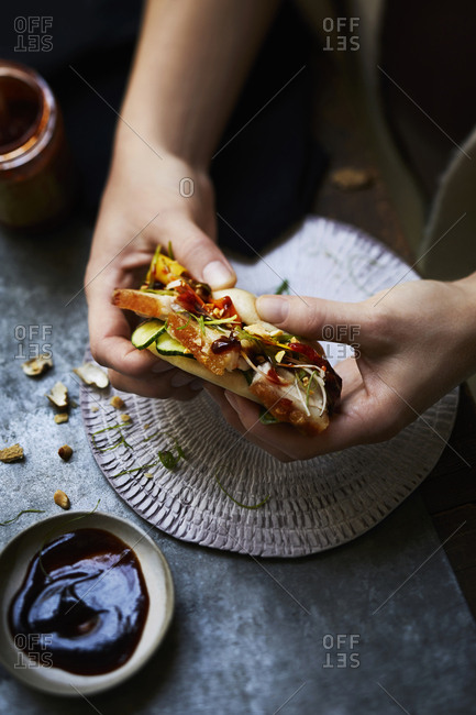 Pork Belly sandwich made with a steam bun and topped with pickled vegetables