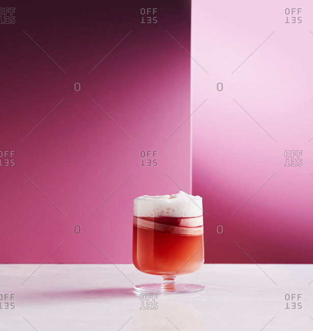 Rhubarb cocktail on a table ageist a pink background