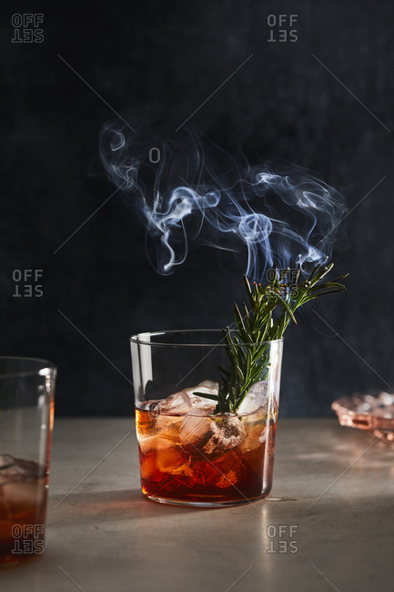 Cocktail with burning rosemary in it