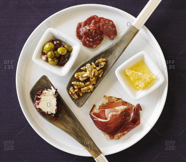 Plate with cured meat, olives, butter, walnuts, cheese