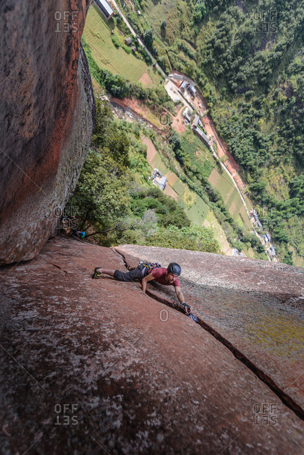 Rock climber climbing sandstone rock, elevated view, Liming, Yunnan Province, China