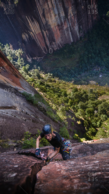 Rock climber climbing sandstone rock, overhead view, Liming, Yunnan Province, China