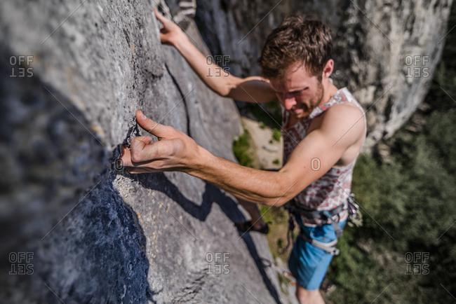 Young male rock climber climbing limestone rock face, Freyr, Belgium, high angle view
