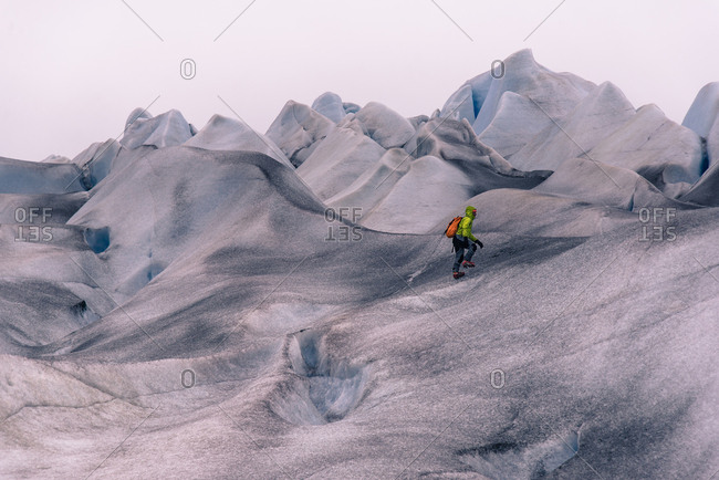 Male hiker hiking over grey snow covered landscape, Narsaq, Vestgronland, South Greenland