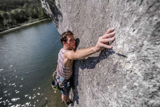 Young male rock climber reaching while climbing limestone rock face, Freyr, Belgium, elevated view