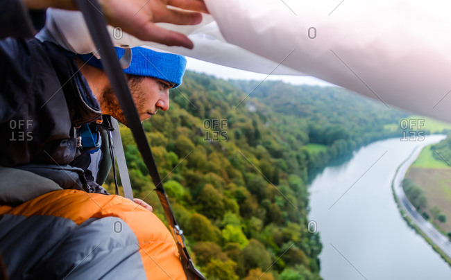 Young male rock climber looking out from rock face portaledge looking out at river Meuse, Freyr, Belgium, elevated view