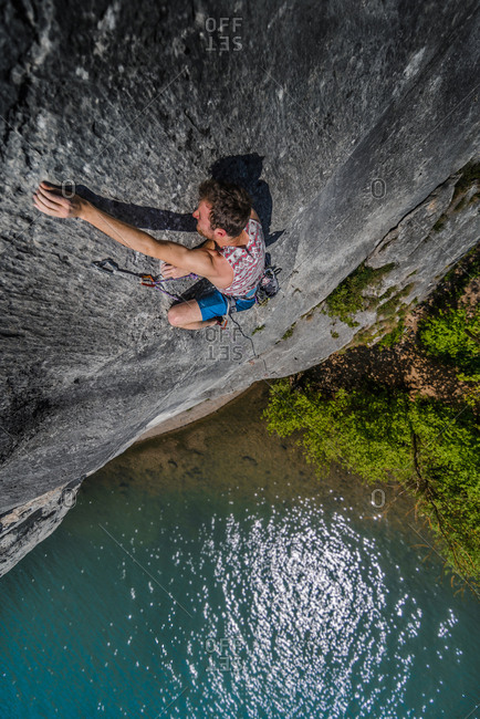 Young male rock climber reaching while climbing limestone rock face, Freyr, Belgium, high angle view