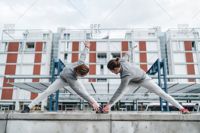 Young adult male twins training together, bent forward stretching