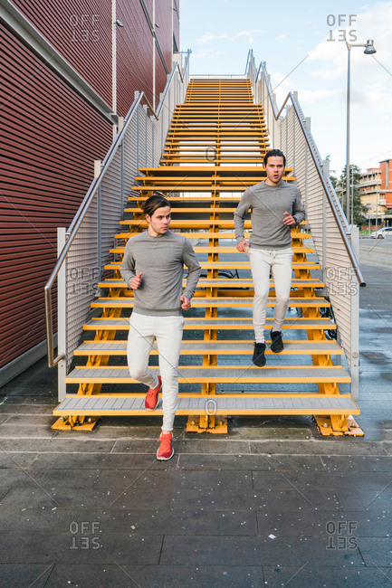 Young adult male twins running together, running down city stairway