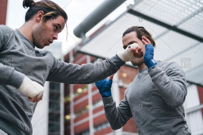 Identical male adult twin boxers training outdoors, practicing punches