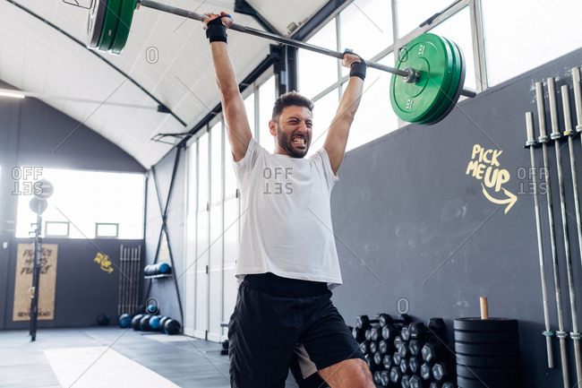 Man weightlifting barbell in gym