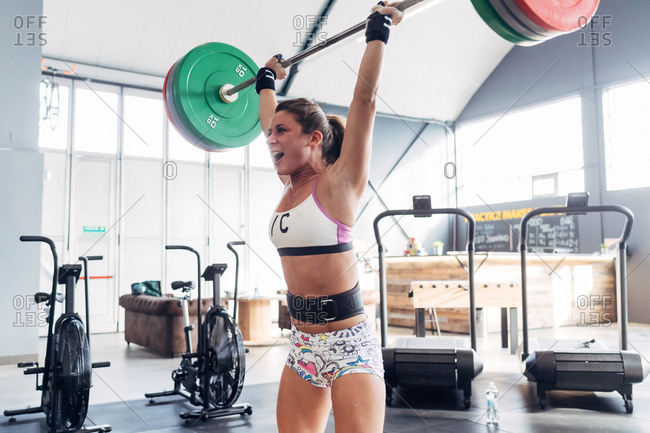 Woman weightlifting barbell in gym