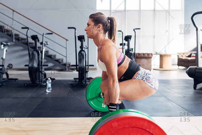 Side view of woman weightlifting barbell in gym