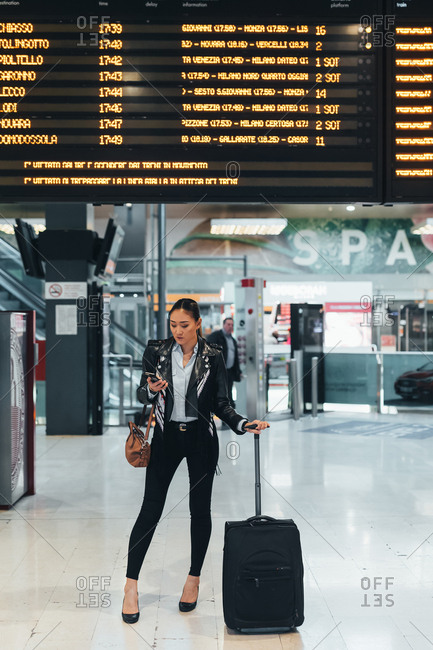 Woman at train station, underneath digital display, holding smartphone and wheeled suitcase