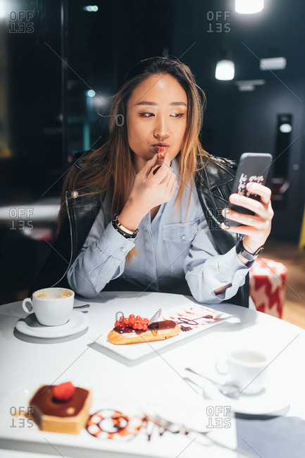 Woman sitting in restaurant, eating dessert, using smartphone