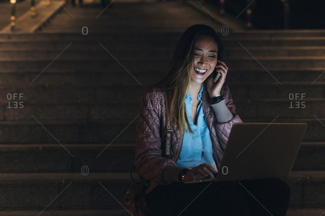 Woman sitting outdoors, on steps, at night, using laptop and smartphone, face illuminated by light from laptop