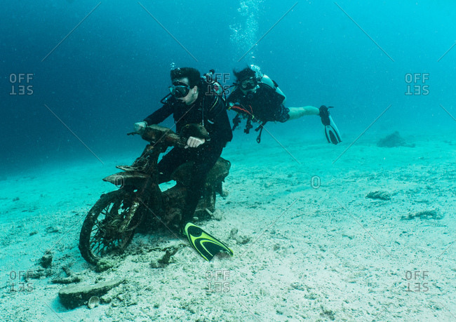 Underwater view of two divers posing on scooter wreck close to Phuket, Thailand