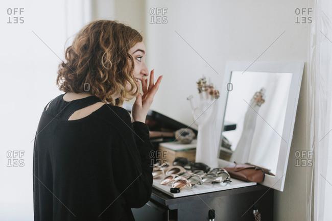Woman at dressing table applying make up