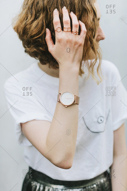 Portrait of red haired woman wearing rings and wristwatch looking away