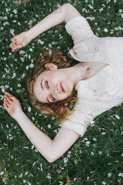 Woman lying down on blossom covered grass, overhead view