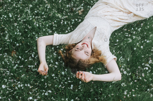 Woman lying down on blossom covered grass