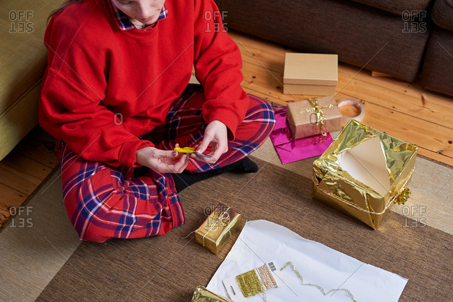 Young woman sitting on living floor wrapping gifts, cropped overhead view