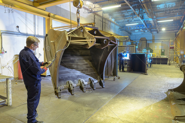 Worker craning large digger bucket into welding bay in engineering factory