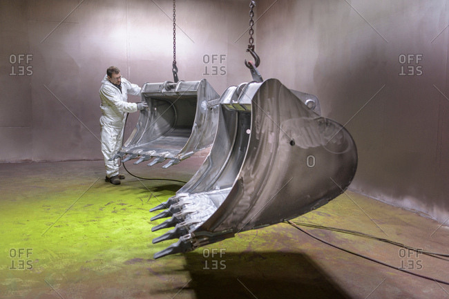 Worker moving digger buckets into spray painting booth in engineering factory