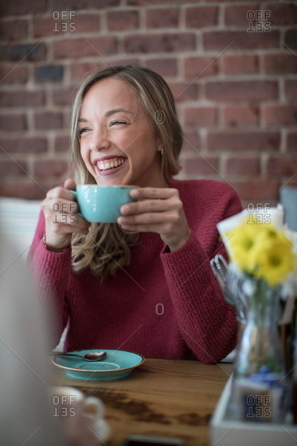 Woman sitting in cafe, drinking coffee, smiling