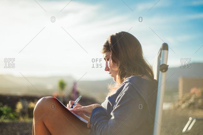 Woman on deckchair writing in journal, Corralejo, Fuerteventura, Canary Islands