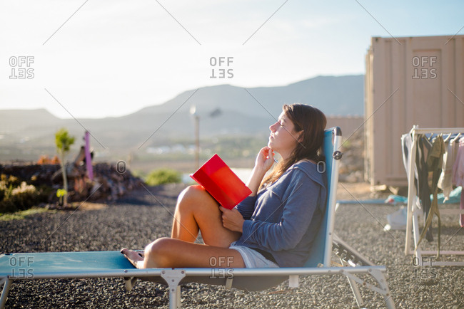 Woman on deckchair, journal in hand, Corralejo, Fuerteventura, Canary Islands
