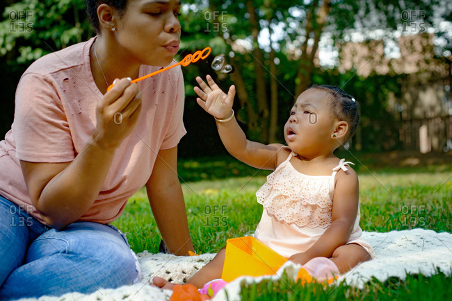 Mid adult woman blowing bubbles in garden for baby daughter