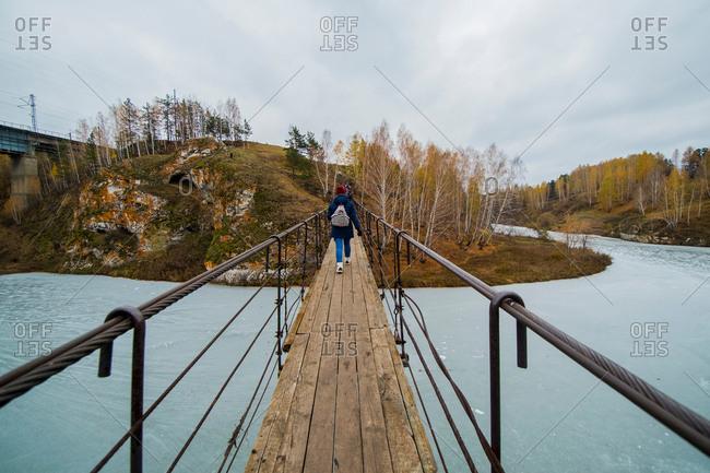 Rear view of small group of hikers walking over river footbridge, Kislokan, Evenk, Russia