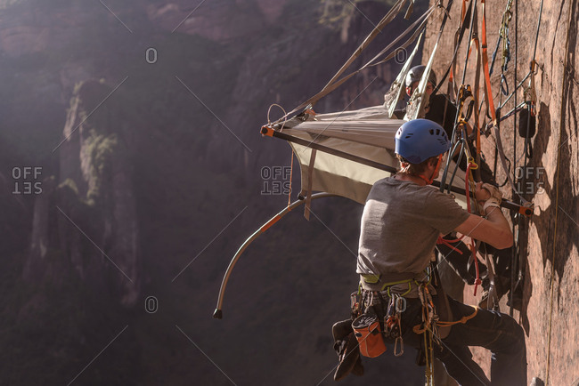 Two rock climbers attaching portaledge to rock, Liming, Yunnan Province, China