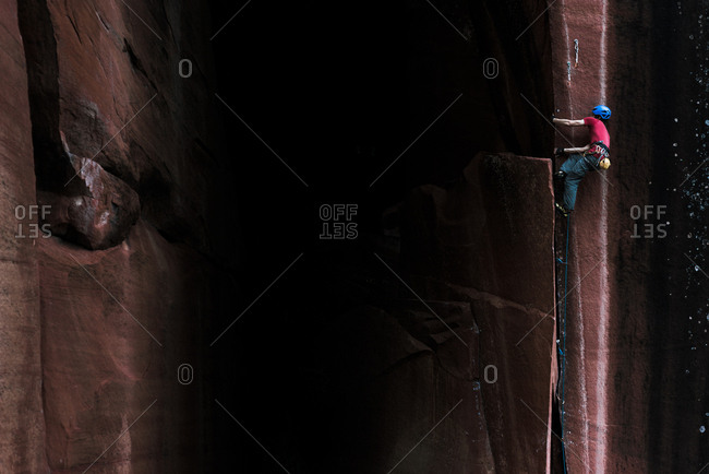 Rock climber climbing sandstone rock, low angle view, Liming, Yunnan Province, China