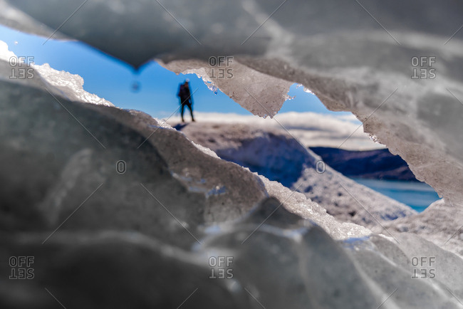 Peek through hole in ice at tourist in distance, Narsaq, Vestgronland, Greenland
