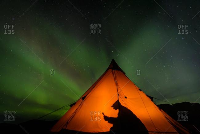 Camper reading inside tent, Aurora Borealis in background, Narsaq, Vestgronland, Greenland